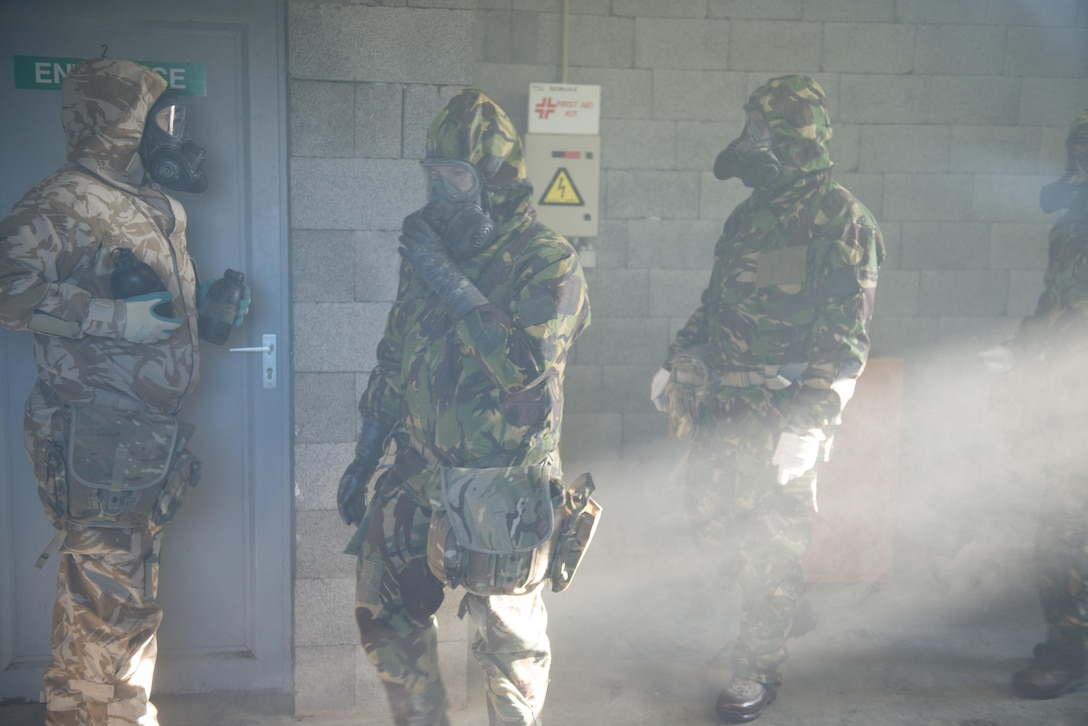 Members of the British armed forces, assigned to different NATO units, walk and adjust their general service respirators inside the U.S. Army Training Support Center Benelux chemical, biological, radiological and nuclear chamber on Chievres Air Base, Belgium, Jan. 19, 2016. British forces assigned to NATO trained under supervision of the British Joint European Training Team. U.S. Army photo by Pierre-Etienne Courtejoie