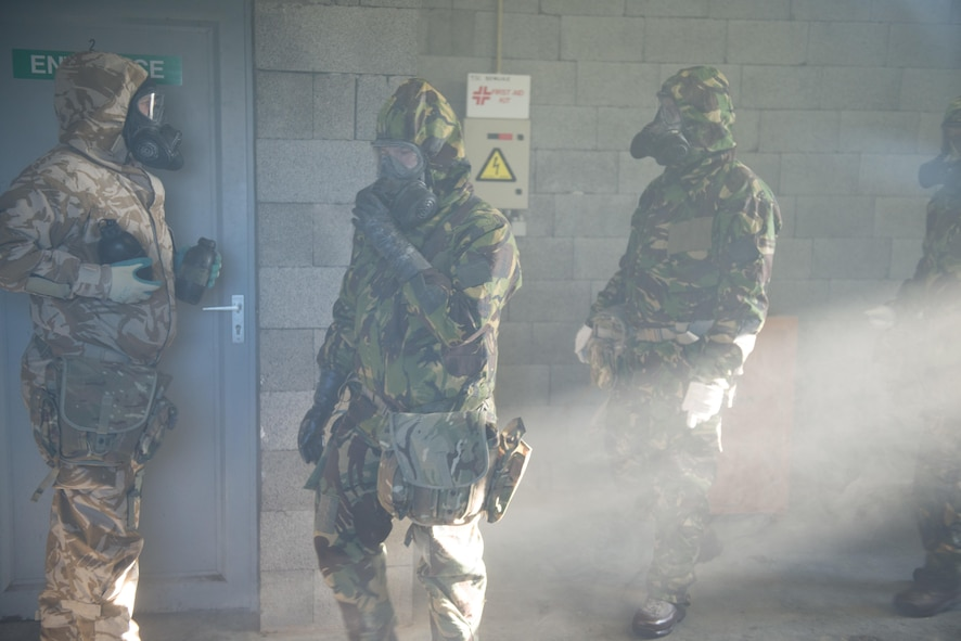 Members of the British armed forces, assigned to different NATO units, walk and adjust their general service respirators.