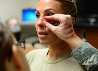 """Tech. Sgt. Catherine Truesdell, 354th Operations Support Squadron noncommissioned officer in charge of Red Flag SARM operations, gets a split lip and choke marks applied to her face and neck Jan. 21, 2016, at Eielson Air Force Base, Alaska. Truesdell volunteered to help raise awareness for domestic violence through the """"Thanks for Asking"""" campaign. (U.S. Air Force photo by Airman 1st Class Cassandra Whitman/Released)"""