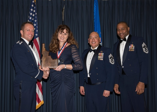Stephanie Hudson accepts the 366th Fighter Wing Spouse Volunteer of the Year award from 366th FW Commander Col. David Iverson, (left) 12th Air Force Command Chief Master Sgt. Jose Barraza and (right) 366th FW Command Chief Master Sgt. David Brown, during the Annual Awards Ceremony at Mountain Home AFB, Idaho, Jan. 29, 2016. (U.S. Air Force photo by Senior Airman Jeremy L. Mosier/Released)