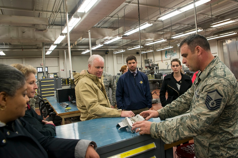 Master Sgt. Timothy Thornton, 437th Maintenance Squadron, metals technology section chief, shows Joint Base Charleston Honorary Commanders an aircraft part that was made by metals technology during a base tour Jan. 22, 2016. The Joint Base Charleston Honorary Commanders Program was developed to encourage an exchange of ideas, experiences and friendship between key members of the local civilian community and the Charleston military community. The program provides a unique opportunity for members of the Charleston area to shadow commanders of wing, group and tenant units at Joint Base Charleston Air Base and Weapons Station. (U.S. Air Force photo/Staff Sgt. William A. O'Brien)