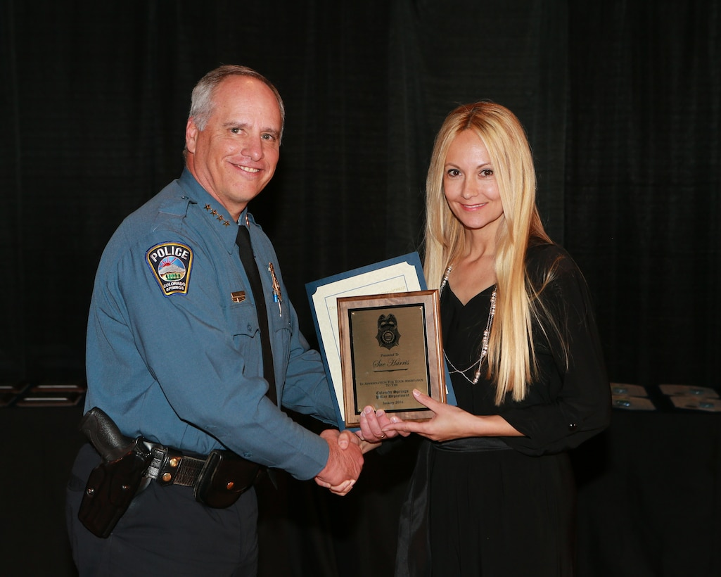 Peter Carey, Colorado Springs police chief, presents Sue Harris with a Citizen's Award of Appreciation during a ceremony Jan. 13, 2016 in Colorado Springs, Colorado. Harris, the wife of Tech. Sgt. Austin Harris, 50th Civil Engineer Squadron, earned the award due to her courageous actions in helping a Colorado Springs police officer apprehend a suspected bank robber. (Courtesy photo)