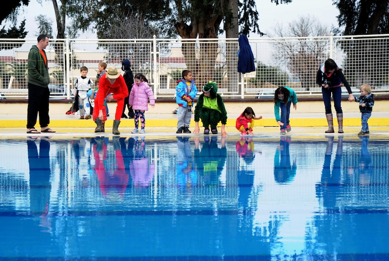 Polar plunge onlookers and participants feel the water as some prepare to jump into the base pool during the polar plunge event Jan. 20, 2016, at Incirlik Air Base, Turkey. The Polar Plunge is an annual event held at Incirlik AB, which gives members an opportunity to dress up in costumes and take a plunge into the cold water of the base pool. (U.S. Air Force photo by Airman 1st Class Daniel Lile/Released)