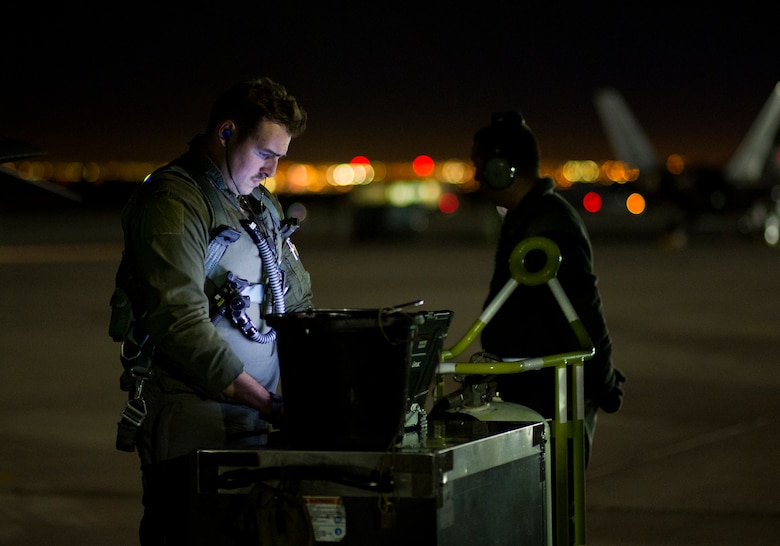 First Lt. Douglas Foss, 95th Fighter Squadron F-22 Raptor pilot, goes through pre-flight procedures during Red Flag 16-1, Jan. 26 at Nellis AFB, Nev. More than 30 squadrons at Red Flag 16-1 are working together as they would in the field, possibly for the first time, before facing an actual threat. (U.S. Air Force photo by Senior Airman Alex Fox Echols III/Released)