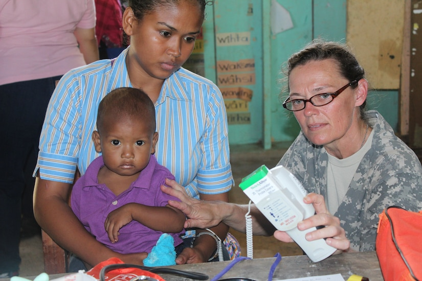 U.S. Army Capt. Penny Wood, a service member with Joint Task Force-Bravo's Medical Element, checks a child's temperature during a Medical Readiness Training Exercise in Nueva Jerusalén, Gracias a Dios Department, Honduras, Jan. 28, 2016. For many mothers, these medical exercises between the U.S. and Honduras are the only opportunity for their children to receive medical attention since health care is limited in the remote region. (U.S. Army photo by Maria Pinel/Released)