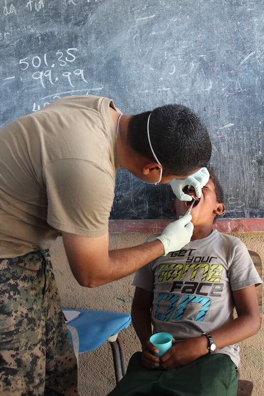 A Honduran soldier performs a tooth extraction from a child during a Medical Readiness Training Exercise between U.S. Service members from Joint Task Force-Bravo and Honduran participants, in Nueva Jerusalén, Gracias a Dios Department, Honduras, Jan. 28, 2016.  These partnerships allow service members to engage with the local community, while supporting local military and local health organizations in remote areas of the country. (U.S. Army photo by Maria Pinel/Released)