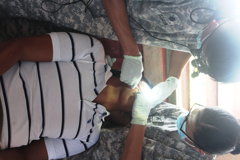 Two Service members with Joint Task Force-Bravo´s Medical Element perform a dental extraction from a patient during a Medical Readiness Training Exercise in Nueva Jerusalén, Gracias a Dios Department, Honduras, Jan. 28, 2016. Though considered an exercise, the MEDRETE provides real services to people in remote areas throughout Central America and gives the U.S. Servicemembers a chance to practice integrating with the local healthcare providers of the nation they visit. (U.S. Army photo by Maria Pinel/Released)
