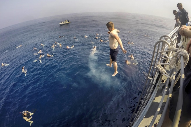 Navy Seaman Curtis Peterson jumps from the fantail of the USS Antietam during a swim call in the Indian Ocean, Feb. 3, 2016. Peterson is a logistics specialist. The Antietam is on patrol to support security and stability in the Indo-Asia-Pacific region. Navy photo by Petty Officer 3rd Class David Flewellyn