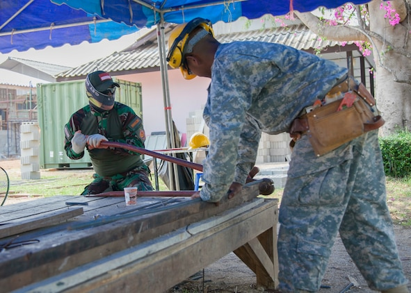 Indonesian Air Force Chief Private Imam Sugiri, with the Engineering Brigade, IAF, cutes rebar as U.S. Army Private 2nd Class James Garcia, with 797th Engineer Company, Vertical, U.S. Army Reserve Center Barrigada, Guam, holds the rebar during the Ban Phromnimit construction project Feb. 2, at Sakeao, Thailand. The construction at Ban Phromnimit is one of six HCA sites in which the Thai, U.S. and partner nation's militaries will work together on civic programs during Cobra Gold 2016. Cobra Gold, in its 35th iteration, demonstrates the commitment of the Kingdom of Thailand and the U.S. to our long-standing alliance and regional partnership toward advancing prosperity and security in the Asia-Pacific region.