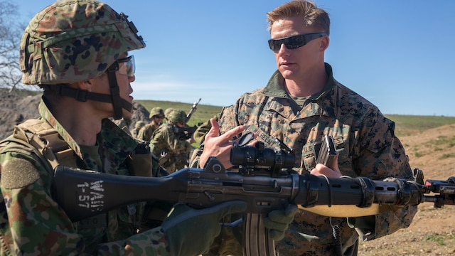 United States Marine Corps Sgt. Mason Wilhelmy, a scout sniper instructor with 1st Marine Division Schools, discusses the Japan Ground Self-Defense Force's Western Army Infantry Regiment's Scout Sniper program with Sgt. First Class Kusumato at Marine Corps Base Camp Pendleton, Calif., Feb. 1, 2016. The two talked about different techniques and methods used to conduct tactical and speed ammunition reloads during an abbreviated scout sniper course at Exercise Iron Fist 2016.The abbreviated scout sniper course gave the U.S. Marines and JGSDF soldiers the opportunity to share their experiences and knowledge and increase camaraderie between the Marine Corps and JGSDF.