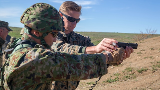 United States Marine Corps Sgt. Mason Wilhelmy, scout sniper instructor, 1st Marine Division Schools, assists a soldier of the Japan Ground Self-Defense Force's Western Army Infantry Regiment's Scout Sniper program with proper pistol grip during an abbreviated scout sniper course, instructed by Marine Corps scout sniper instructors, during Exercise Iron Fist 2016 on Marine Corps Base Camp Pendleton, Calif., Feb. 1, 2016. Iron Fist is an annual, bilateral amphibious training exercise designed to improve the Marine Corps and JGSDF's ability to plan, communicate and conduct combined amphibious operations. Operating in small teams, scout snipers can be used to conduct reconnaissance and eliminate targets prior to an amphibious assault.