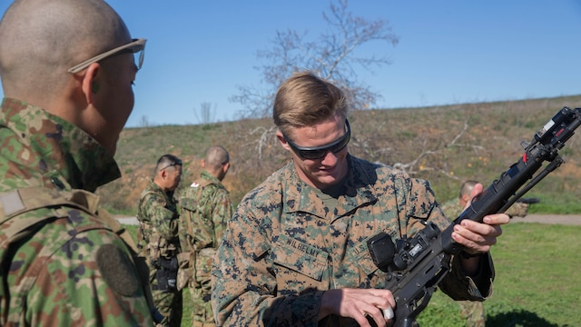 Sergeant 1st Class Yusuke Irie of the Japan Ground Self-Defense Force, Western Army Infantry Regiment watches as U. S. Marine Corps Sgt. Mason Wilhelmy, a scout sniper instructor with 1st Marine Division Schools, gets a hands-on review of the JGSDF weapons during an abbreviated scout sniper course held during Exercise Iron Fist 2016, on Marine Corps Base Camp Pendleton, Calif., Feb. 1, 2016. The course offers the U.S. Marines and JGSDF soldiers the opportunity to share their experiences and knowledge and increase camaraderie between the Marine Corps and JGSDF in a bilateral training environment.