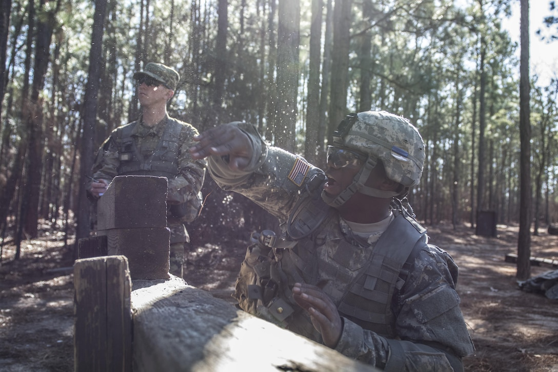 Army Drill Sergeant, Staff Sergeant Jonathan Martin, C Company, 1st Battalion, 61st Infantry Regiment watches as a Solider in basic combat training tosses a practice grenade from the kneeling position on the hand grenade assault course at Fort Jackson, S.C., Feb. 1, 2016. (U.S. Army photo by Sgt. 1st Class Brian Hamilton)