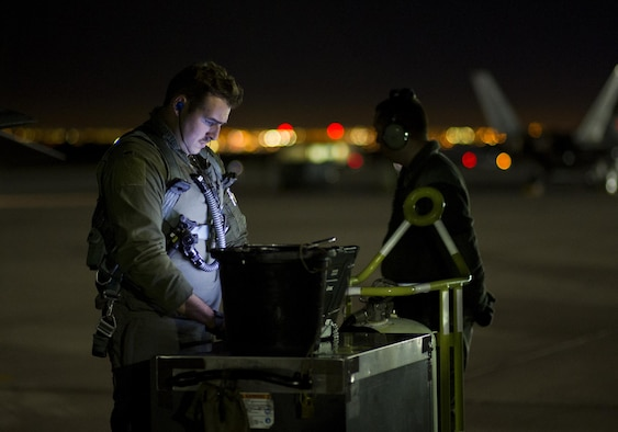 First Lt. Douglas Foss, a 95th Fighter Squadron F-22 Raptor pilot, goes through preflight procedures during Red Flag 16-1, Jan. 26, 2016, at Nellis Air Force Base, Nev. More than 30 squadrons at Red Flag 16-1 worked together, some for the first time, training and preparing for a variety of possible threats. (U.S. Air Force photo/Senior Airman Alex Fox Echols III)