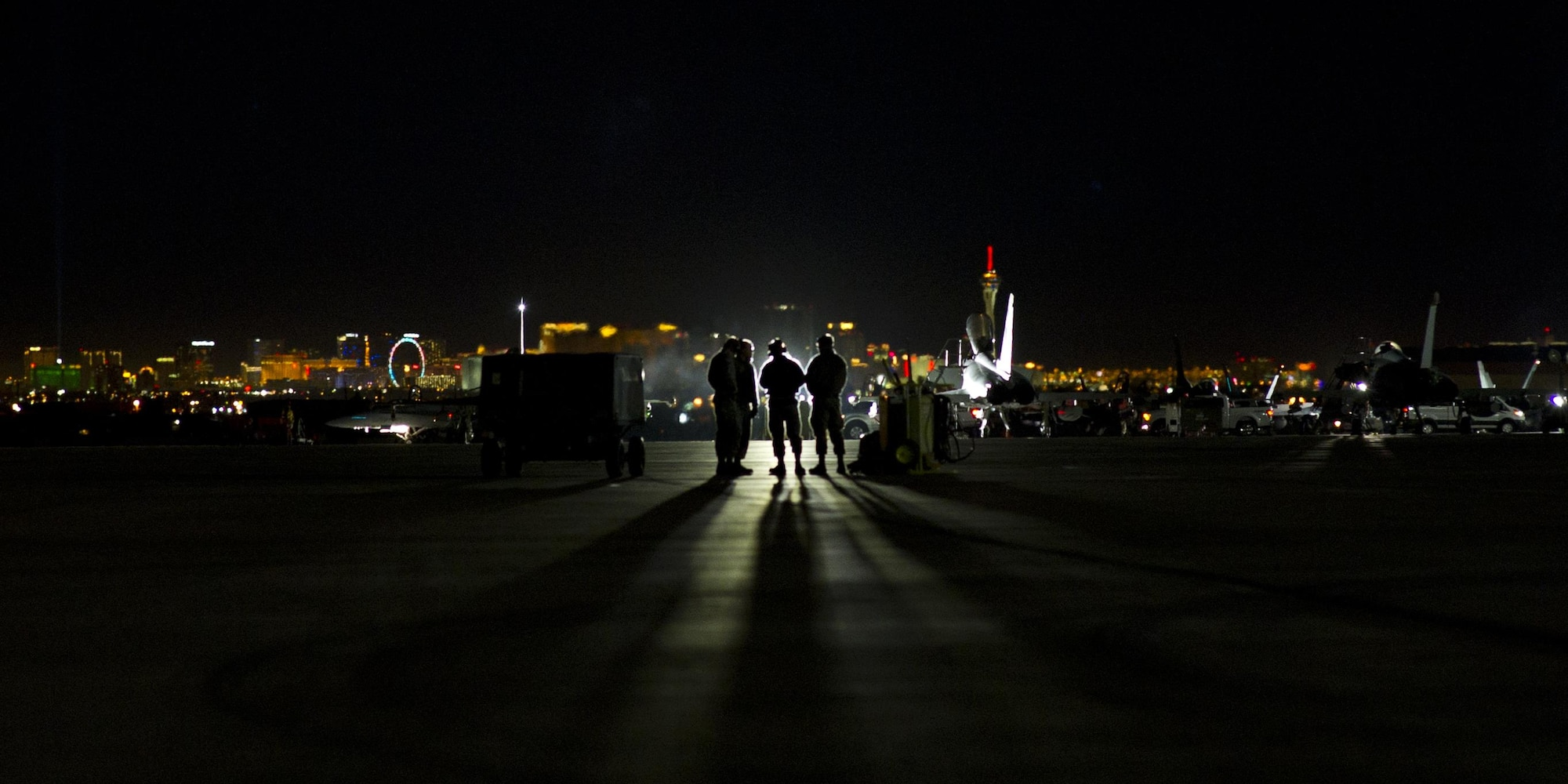 Four Airmen stand on the flightline looking toward the lights of Las Vegas Jan. 26, 2016, at Nellis Air Force Base, Nev. The Airmen were part of more than 3,000 personnel from over 30 units, including squadrons from Australia and the U.K., to participate in Red Flag 16-1. (U.S. Air Force photo/Senior Airman Alex Fox Echols III)