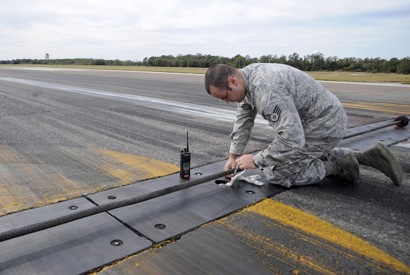 Staff Sgt. Michael David, an airfield management operations supervisor with the 6th Operations Support Squadron, removes a loose rope found on the flightline during a routine check at MacDill Air Force Base, Fla., Jan. 22, 2016. Airfield management Airmen must stay vigilant in order to detect a wide variety of safety hazards. (U.S. Air Force photo/Airman 1st Class Mariette M. Adams)