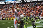 Jimmy Graham, left, tight end for the New Orleans Saints, catches a touchdown pass from Drew Brees, quarterback for the New Orleans Saints, during the 2014 NFL Pro Bowl at Aloha Stadium, Hawaii, Jan. 26, 2014. U.S. Marine Corps photo by Lance Cpl. Matthew Bragg