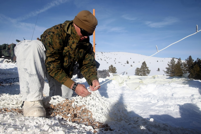 Cpl. Robert Schmitt sews an artic camouflage net during cold weather training at Marine Corps Mountain Warfare Training Center, Calif., Jan. 21, 2016. The cold weather training done in the Sierra Mountains is a warm-up to Exercise Cold Response 1-16 in Norway. Nearly 80 Marines with 2nd LAAD Bn. participated in the two-weeklong exercise that taught basic mobility in snow, defensive and offensive tactics as well as basic cold weather and high altitude conditions training.