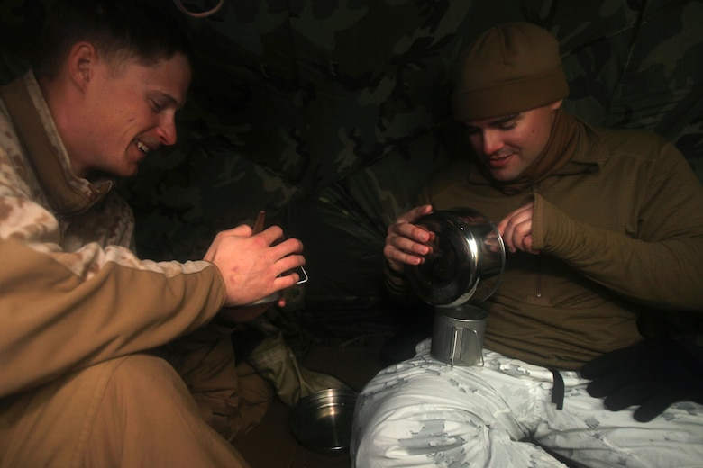 Cpl. Timothy J. Langendorfer share noodles with Cpl. Robert J. Schmitt after utilizing the water procurement skills they learned during cold weather training at Marine Corps Mountain Warfare Training Center, Calif., Jan. 21, 2016. The cold weather training done in the Sierra Mountains is a warm-up to Exercise Cold Response 1-16 in Norway. Nearly 80 Marines with 2nd LAAD Bn. participated in the two-weeklong exercise that taught basic mobility in snow, defensive and offensive tactics as well as basic cold weather and high altitude conditions training. Langendorfer and Schmitt are both low altitude air defense gunners with 2nd Low Altitude Air Defense Battalion.