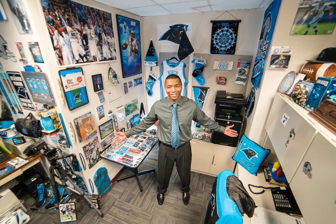 Sidney A. Williams Jr., the support services supervisor for the Defense Information School on Fort Meade, stands in his office at the school. Williams, who grew up in North Carolina, has filled the office with Carolina Panthers memorabilia, including a picture of a Panthers player that his son, Michael D. Williams, now 19, drew for him when he was 10, and a framed jersey autographed by Cam Newton, the star quarterback for the team.