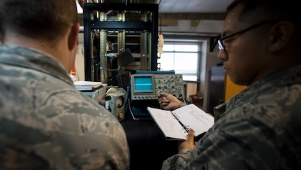 Staff Sgt. Michael Reyes, 437th Operations Support Squadron airfield systems technician, reads a technical order to Tech. Sgt. Shawn Arnett, 437th OSS airfield systems technician Jan. 27, 2016, at the command tower on Joint Base Charleston – North Auxiliary Air Field, S.C. This two-man team ensures that all of their airfield systems located at North Field work properly and provide any maintenece when needed. (U.S. Air Force photo/Senior airman Clayton Cupit)