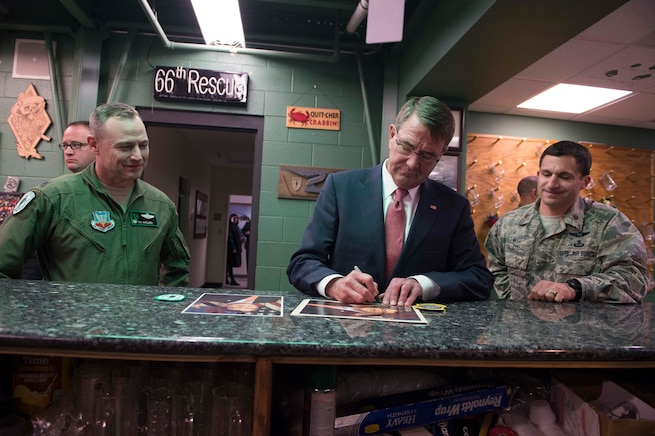 Defense Secretary Ash Carter, center, autographs a photo at the 66th Rescue Squadron headquarters on Nellis Air Force Base, Nev., Feb. 4, 2016. DoD photo by Navy Petty Officer 1st Class Tim D. Godbee
