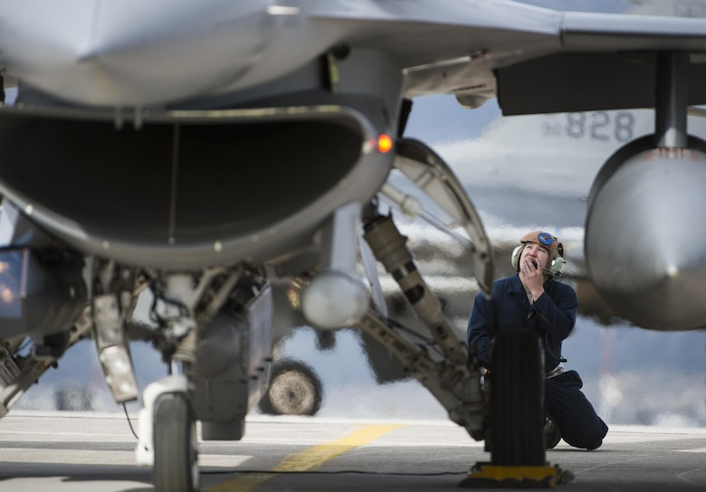 Staff Sgt. Ryan Anderson, a crew chief assigned to the 480th Expeditionary Fighter Squadron, performs preflight checks while communicating with an F-16 Fighting Falcon pilot before departure from the flightline at Souda Bay, Greece, Jan. 27. 2016. Anderson, along with 300 personnel from Spangdahlem Air Base, Germany, were participating in the flying training deployment between the Hellenic and U.S. air forces at Souda Bay from Jan. 22 to Feb. 15, 2016. (U.S. Air Force photo/Staff Sgt. Christopher Ruano)
