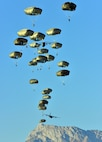 Army paratroopers descend onto Juliet drop zone in Pordenone, Italy, Jan. 21, 2016, during airborne operations training. Army photo by Paolo Bovo