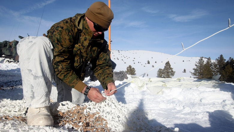 Cpl. Robert Schmitt sews an Arctic camouflage net during cold weather training at Marine Corps Mountain Warfare Training Center, California, Jan. 21, 2016. The cold weather training done in the Sierra Mountains is a warm-up to Exercise Cold Response 1-16 in Norway. Nearly 80 Marines with 2nd LAAD Bn. participated in the two-weeklong exercise that taught basic mobility in snow, defensive and offensive tactics as well as basic cold weather and high altitude conditions training.