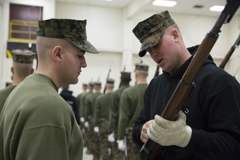Lance Cpl. Cody McNeley, a Silent Drill School instructor, conducts baseline drill sequence training, called landing party manual, with a student at Joint Base Anacostia, Washington, D.C., Jan. 8, 2016. Each year from November to March the Silent Drill Platoon conducts Silent Drill School to hand-select new Marines for the upcoming parade season.  The selection process is conducted by Marines from previous years to identify Marines who will represent, on the parade deck, the professionalism associated with the Marine Corps. (Official Marine Corps photos by Cpl. Chi Nguyen/Released)