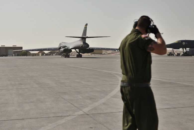 Staff Sgt. Bryant, 28th Aircraft Maintenance Squadron crew chief, watches as his B-1 bomber moves towards the flightline for take-off Sept. 22, 2015 at Al Udeid Air Base, Qatar. Bryant was deployed out of Ellsworth Air Force Base, S.D. (U.S. Air Force photo by Staff Sgt. Alexandre Montes/Released)