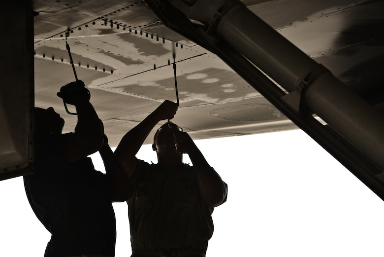 Tech. Sgt. Nasir and Airman 1st Class James, 28th Aircraft Maintenance Squadron crew chiefs, remove a panel underneath a B-1 bomber to check for leaks as part of a final pre-flight inspection Sept. 22, 2015 at Al Udeid Air Base, Qatar. Nasir and James were deployed from Ellsworth Air Force Base, S.D. (U.S. Air Force photo by Staff Sgt. Alexandre Montes/Released)