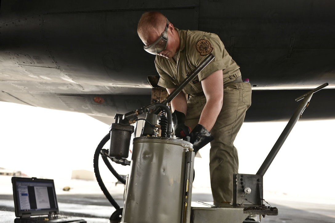 Airman 1st Class James, 28th Aircraft Maintenance Squadron crew chief, fills the auxiliary power unit of a B-1 bomber as part of his final inspections to ready the aircraft before an aircrew boards for a mission Sept. 22, 2015 at Al Udeid Air Base, Qatar. James was deployed to the area from Ellsworth Air Force Base, S.D. (U.S. Air Force photo by Staff Sgt. Alexandre Montes/Released)