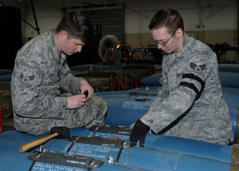 Airman 1st Class Dylan Giron, left, and Senior Airman Jesse Knappen, 28th Munitions Squadron crew members, apply a lanyard to a bomb dummy unit-50 as part of the delayed timer unit during a training session at Ellsworth Air Force Base, S.D., Jan. 19, 2016. The 28th MUNS consists of more than 240 Airmen working in four flights, providing support for the 27 B-1 bombers assigned to Ellsworth AFB. (U.S. Air Force photo by Airman 1st Class Denise M. Nevins/Released)