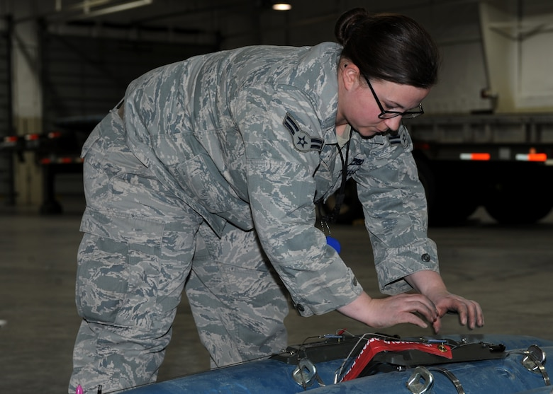 Airman 1st Class Lauren Sessums, 28th Munitions Squadron crew member, installs a delayed timer unit to a bomb dummy unit-50 during a training session at Ellsworth Air Force Base, S.D., Jan. 19, 2016. The DTU allows a pillow parachute to be deployed from the munition, enabling the bomb to detonate at lower altitudes for a close ground attack. (U.S. Air Force photo by Airman 1st Class Denise M. Nevins/Released)