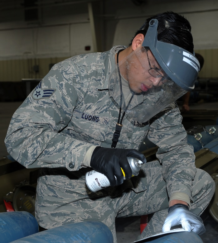 Senior Airman John Luong, 28th Munitions Squadron munitions inspector, spray-paints a weapon serial number on a bomb dummy unit-50 during a training session at Ellsworth Air Force Base, S.D., Jan. 19, 2016. The WSN is used to label munitions from different pallets so if there was a malfunction it could be easier to determine if it was a technical error or factory issue. (U.S. Air Force photo by Airman 1st Class Denise M. Nevins/Released)