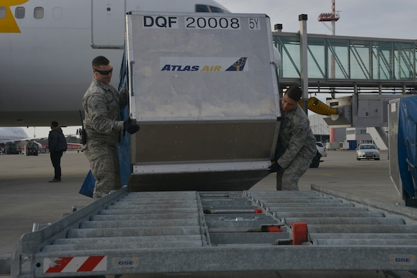 Senior Airman Cornel Griffen and Airman 1st Class Paul Boughner, 721st Aerial Port Squadron passenger service agents, load cargo containers onto a platform Jan. 27, 2016, at Ramstein Air Base, Germany. These platforms are used to quickly transport cargo around the flightline. (U.S. Air Force photo/Airman 1st Class Lane T. Plummer)
