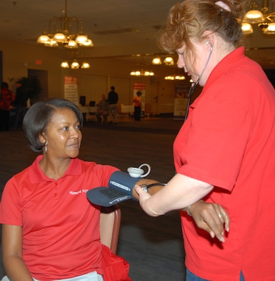 Angela Hawkins, Tricare representative, has her blood pressure checked by Kelley Denny, Civilian Health Promotions Services coordinator, as part of her Cardiac Risk Profile at last