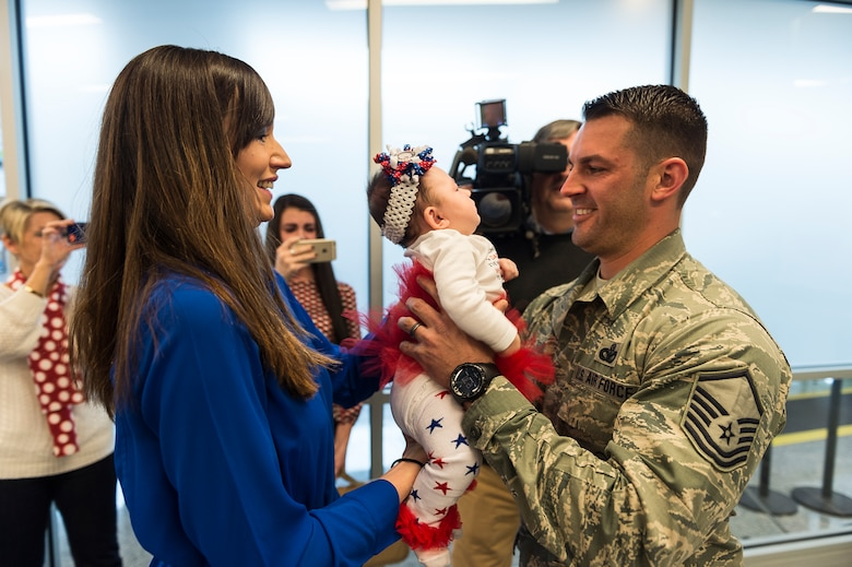 Master Sgt. Daniel Owczarczak, an Airman assigned to the 107th Security Forces Squadron, Niagara Falls Air Reserve Station, N.Y., gets to see his newborn daughter for the first time. Owczarczak was one of more than 30 Airmen from the 107th SFS to return from a six-month deployment to Southwest Asia, Feb. 4-5, 2016. (U.S. Air National Guard photo by Staff Sgt. Ryan Campbell/Released)