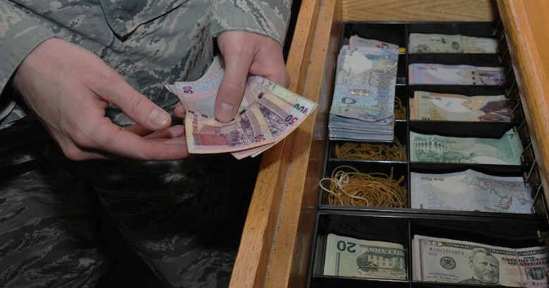 Senior Airman Bryan Hersey, 379th Expeditionary Comptroller Squadron cashier from Lompoc, California, counts Qatari Riyal while working inside the cashier cage at Al Udeid Air Base, Qatar, Jan. 24. Hersey said one of the most popular services the 379 ECPTS provides is currency exchanges and he's disbursed more than $4 million over the past six months. He said he loves his job because he enjoys helping people. (U.S. Air Force photo by Tech. Sgt. James Hodgman/Released)