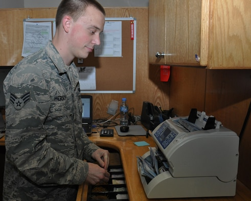 Senior Airman Bryan Hersey, a 379th Expeditionary Comptroller Squadron cashier from Lompoc, Calif., counts Qatari Riyal while working inside the cashier cage at Al Udeid Air Base, Qatar, Jan. 24, 2016. One of the most popular services the 379th ECPTS provides is currency exchanges. (U.S. Air Force photo/Tech. Sgt. James Hodgman)