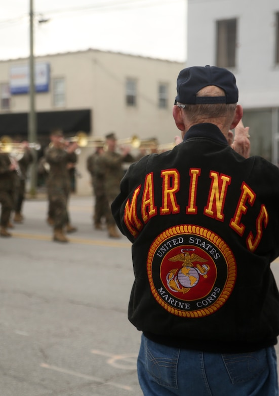 A former Marine claps as active-duty service members with 2nd Marine Division march in the Division's 75th anniversary parade in downtown Jacksonville, N.C., Feb. 6, 2016. The celebration serves as a time to remember the Marines and sailors who served and continue to serve in 2nd Marine Division, while thanking the local community for their support. (U.S. Marine Corps photo by Cpl. Joey Mendez/Released)