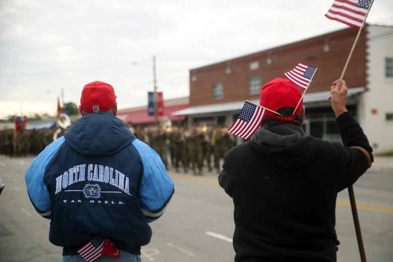 Veteran Marines wave American flags as active-duty service members with 2nd Marine Division march in the Division's 75th anniversary parade in downtown Jacksonville, N.C., Feb. 6, 2016. The celebration serves as a time to remember the Marines and sailors who served and continue to serve in 2nd Marine Division, while thanking the local community for their support. (U.S. Marine Corps photo by Cpl. Joey Mendez/Released)