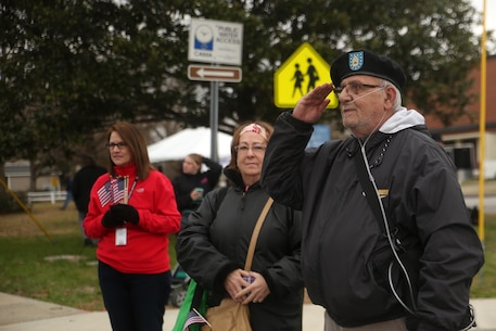 A retired Army Sergeant First Class salutes as Marines and sailors with 2nd Marine Division march in the unit's 75th anniversary parade through downtown Jacksonville, N.C., Feb. 6, 2016. The celebration serves as a time to remember the Marines and sailors who served and continue to serve in 2nd Marine Division, while thanking the local community for their support. (U.S. Marine Corps photo by Cpl. Joey Mendez/Released)