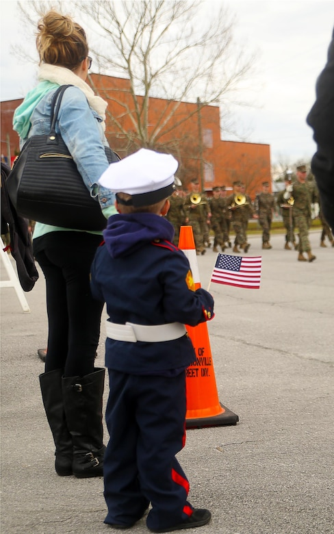 A young boy watches as Marines with 2nd Marine Division march in the unit's 75th anniversary parade in downtown Jacksonville, N.C., Feb. 6, 2016. The celebration serves as a time to remember the Marines and sailors who served and continue to serve in 2nd Marine Division, while thanking the local community for their support. (U.S. Marine Corps photo by Cpl. Joey Mendez/Released)