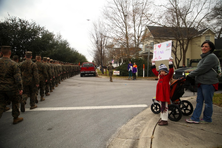 A young girl displays a sign to show support for 2nd Marine Division during the unit's 75th anniversary parade in downtown Jacksonville, N.C., Feb. 6, 2016. The celebration serves as a time to remember the Marines and sailors who served and continue to serve in 2nd Marine Division, while thanking the local community for their support. (U.S. Marine Corps photo by Cpl. Joey Mendez/Released)