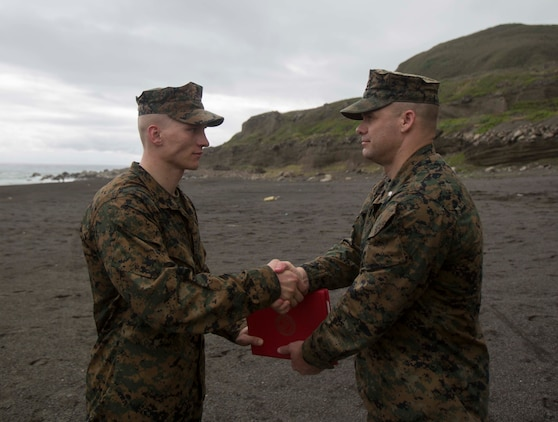 U.S. Marine Corps Sgt. Cody R. Gannon, a mortarman with Bravo Company, 1st Battalion, 2nd Marine Regiment, is meritoriously promoted by Lt. Col. Eric A. Reid, the battalion commander of 1/2, on Iwo Jima, Japan, Feb. 2, 2016. Gannon won the 2nd Marine Division Meritorious Sergeant Board and is currently forward deployed in the Pacific as part of 3rd Marine Division. (U.S. Marine Corps photo by MCIPAC Combat Camera Lance Cpl. Robert Gonzales/Released)