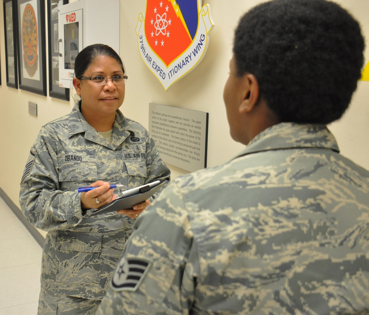 Air Force Master Sgt. Janine Obando, the 379th Air Expeditionary Wing's equal opportunity director, left, meets with Air Force Staff Sgt. Yolanda Jackson, the noncommissioned officer in charge of 379th AEW protocol on Al Udeid Air Base, Qatar, Jan. 21, 2016. Obando, who hails from Ewa, Hawaii, said it's important to meet with service members to foster trust between units and the EO office. Air Force photo by Tech. Sgt. James Hodgman