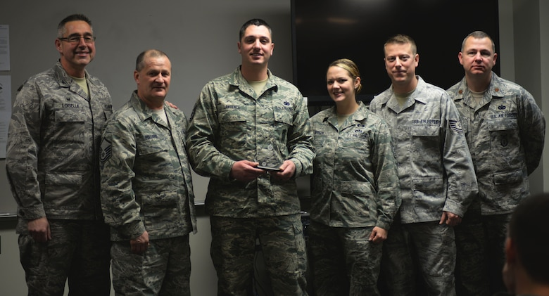 Staff Sgt. Paul Lawrence, (center), 157th Security Forces Squadron craftsman, was named the New Hampshire Air National Guard Unit Career Advisor (UCA) of the Year during the security forces roll call, Pease Air National Guard Base, N.H., Jan. 2, 2016. (U.S. Air National Guard photo by Senior Airman Kayla McWalter)