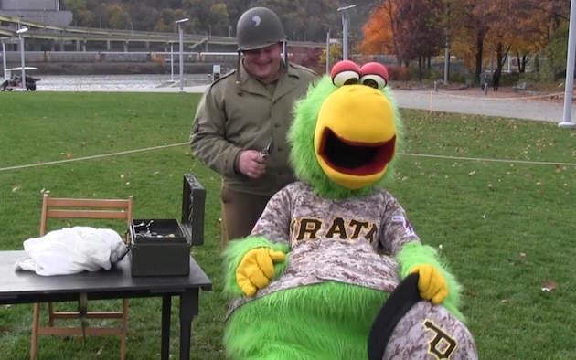 The Pirate Parrot gets a trim and a shave by a World War II field barber. The Pennsylvania National Guard joined with the Pennsylvania Department of Conservation of Natural Resources' Point State Park and the Association of the United States Army to organize Steel City Salutes the Troops, Pittsburgh, Nov. 7, 2015.  (U.S. Air National Guard Photo by Staff Sgt. Ryan Conley)